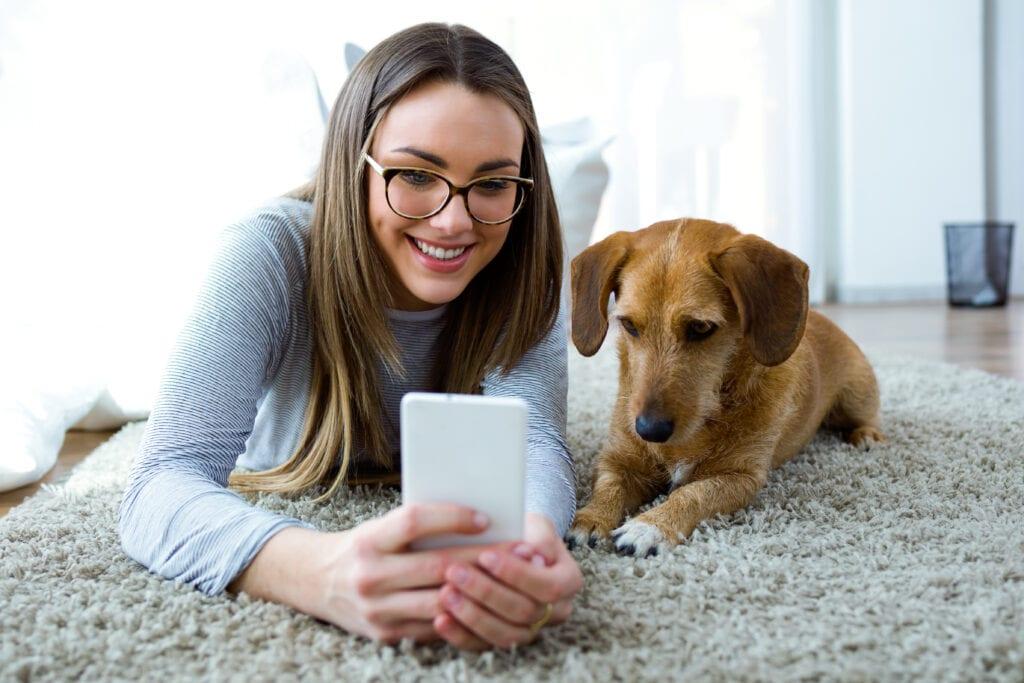 Woman and Dog Looking at Phone